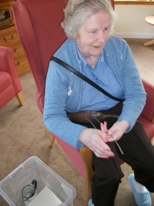 Helen Sheed showing the group how to use a wisker when knitting a sweater