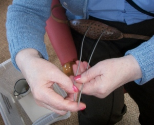 A close-up of Helen Sheed showing the group how to use a wisker when knitting a sweater
